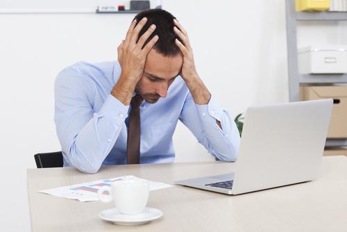 パソコンを前に悩む男性