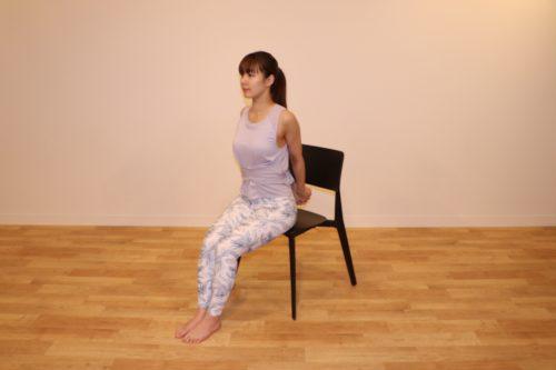 椅子に座り、両手を後ろで組んでいるところ