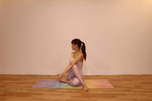 床に両手をつき、右足をねじって左足の外に置いているところから、さらに左手を右側に伸ばし、首を右後ろにねじっているところ