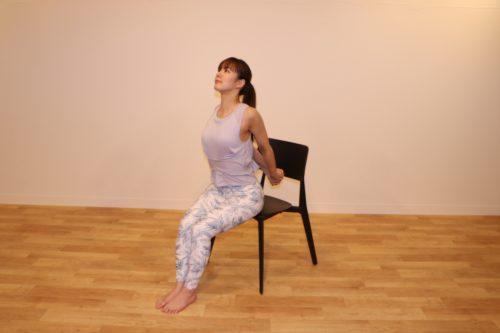 椅子に座って両手を後ろで組み、状態をぐっと前にそらしているところ