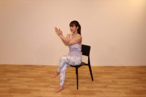 椅子に座って足を組み、両腕を交差させて上に向けているところ