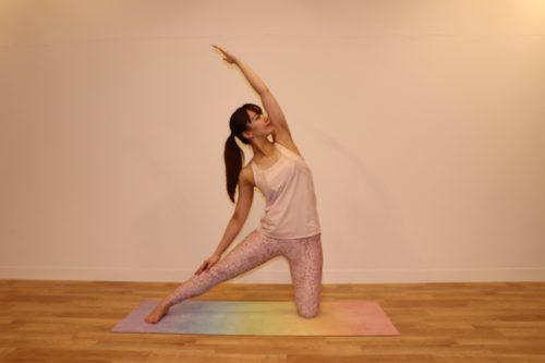 左の膝を床につき、右足をまっすぐ横へ伸ばして、顔を左側に向けて左腕を上へ伸ばしているところ