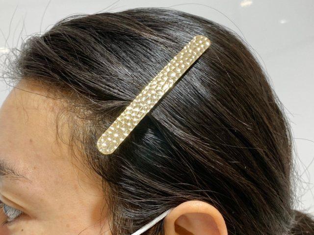 メタル槌目をヘアアクセサリーとして使う女性