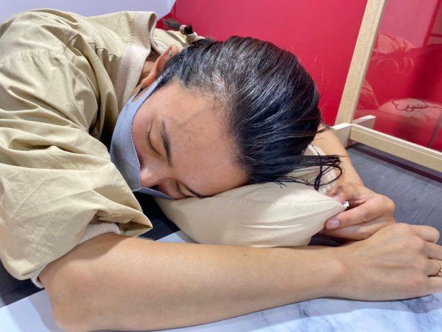 くまのプーさんクッションで寝る女性