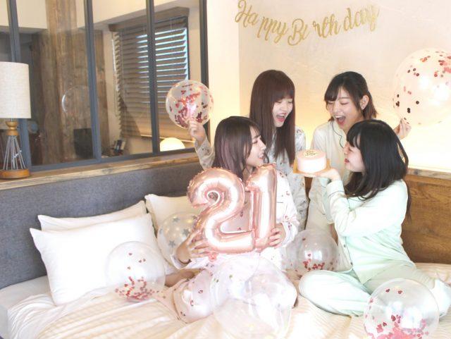 ベッドの上でバルーンやケーキを持つ女性たち