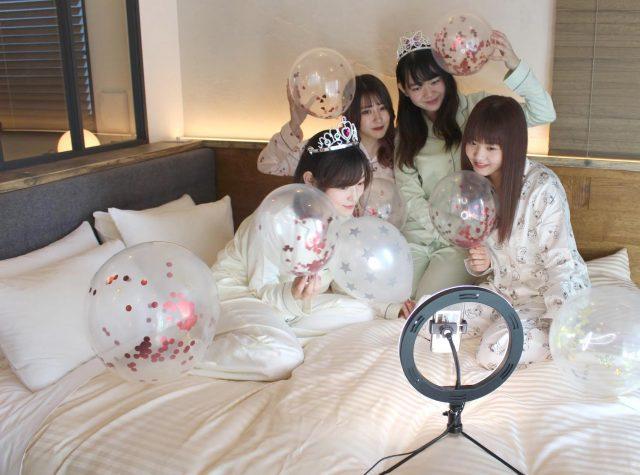 ベッドの上でスマホに向かってポーズをとる女性たち