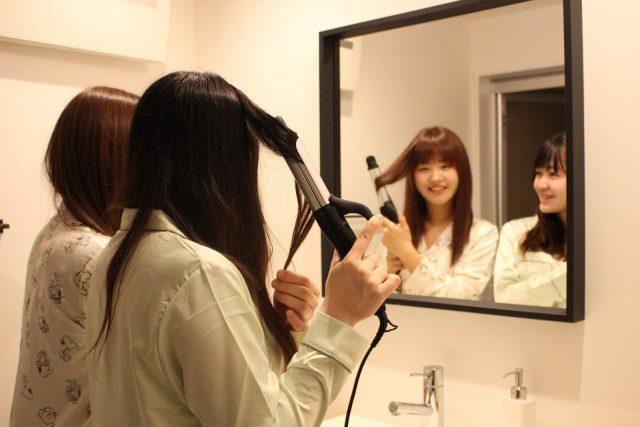 鏡の前でヘアアイロンを使う女性たち