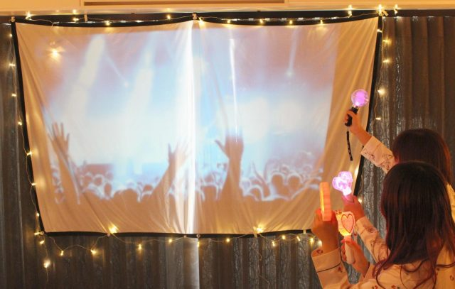 プロジェクターに映したコンサートで盛り上がる女性たち