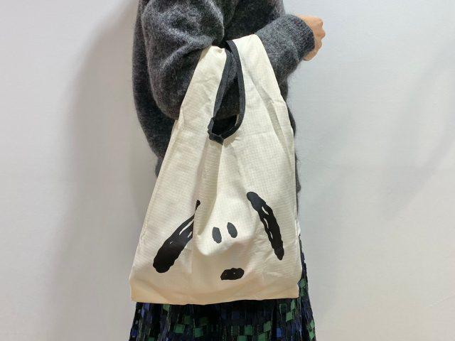 スヌーピーのエコバッグを持った女性