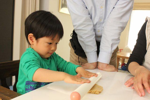 ピザを作る男の子と家族