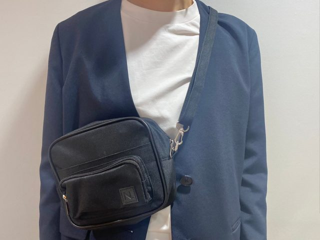 N. Natural Beauty Basic 10ポケットショルダーバッグを短めの斜めがけにした女性