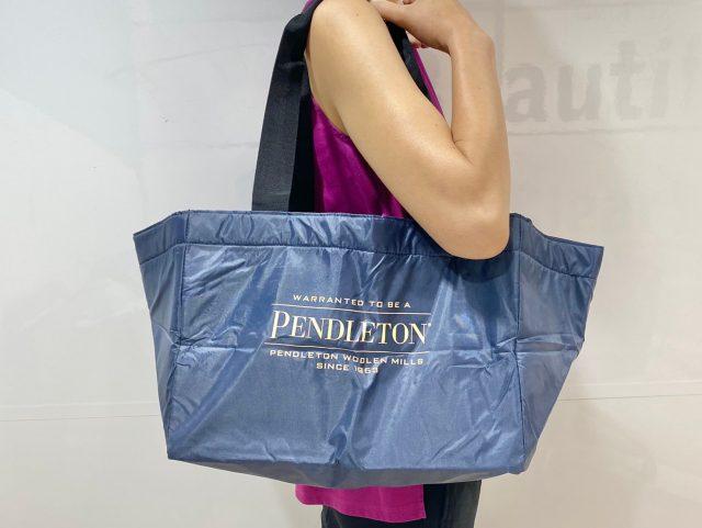 PENDLETON 保冷ができるBIG SHOPPING BAG(ネイビー)を肩にかけた女性