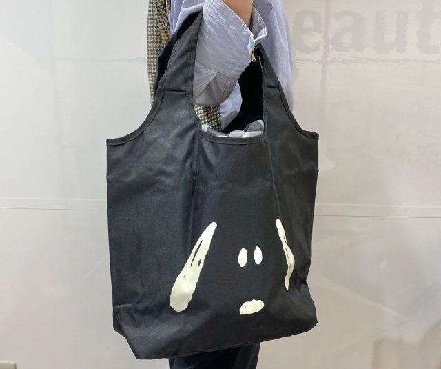 スヌーピーとチャーリー・ブラウンのDOUBLE FACE BAGを腕にかけた女性