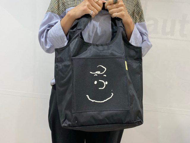 スヌーピーとチャーリー・ブラウンのDOUBLE FACE BAGを持った女性